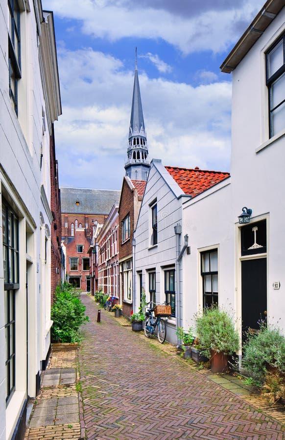 O corredor pequeno com branco emplastrou casas e uma igreja no fundo, Gouda, Países Baixos imagens de stock