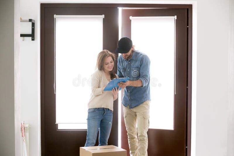 O correio traz uma entrega do pacote à mulher do cliente imagens de stock