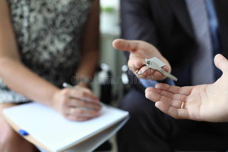 O corretor de imóveis está cedendo a chave do apartamento novo fotografia de stock royalty free