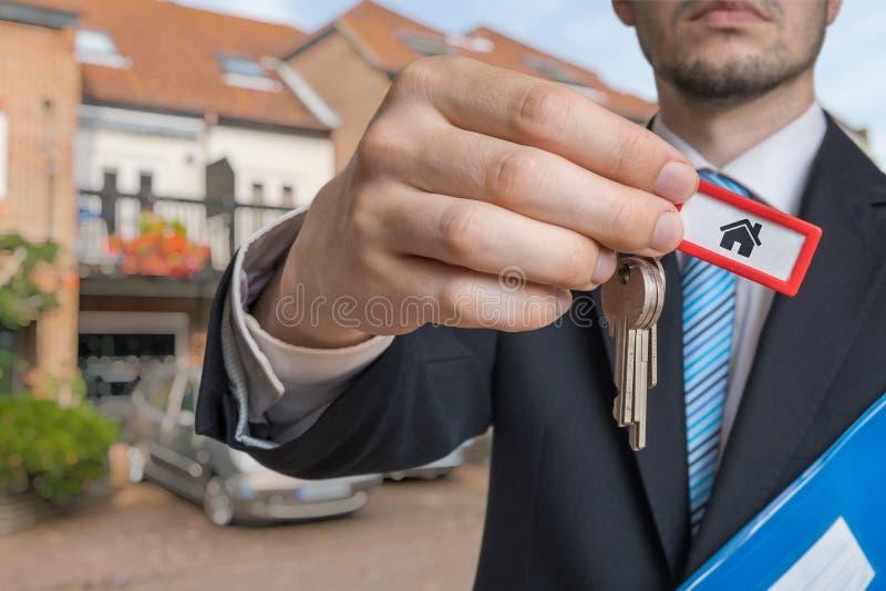 O corretor de imóveis está vendendo a casa e está dando-lhe chaves fotografia de stock royalty free