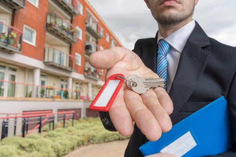 O corretor de imóveis está vendendo a casa e está dando-lhe chaves fotografia de stock