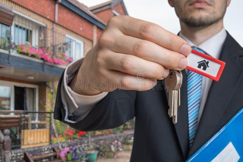 O corretor de imóveis está vendendo a casa e está dando-lhe chaves imagem de stock royalty free