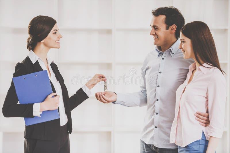 O corretor de imóveis fêmea está dando aos pares novos uma chave do plano novo foto de stock royalty free