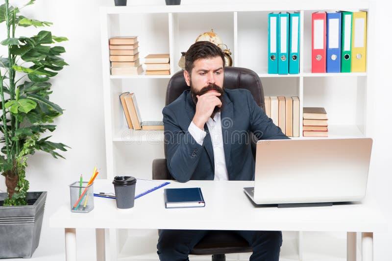 O corretor segue indicadores financeiros O chefe farpado do moderno do homem senta-se no interior de couro do escritório da poltr fotos de stock