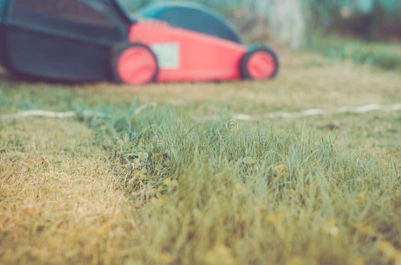 O cortador de grama é limpado de uma grama/cortador de grama é limpado de uma grama Foco seletivo toned fotografia de stock