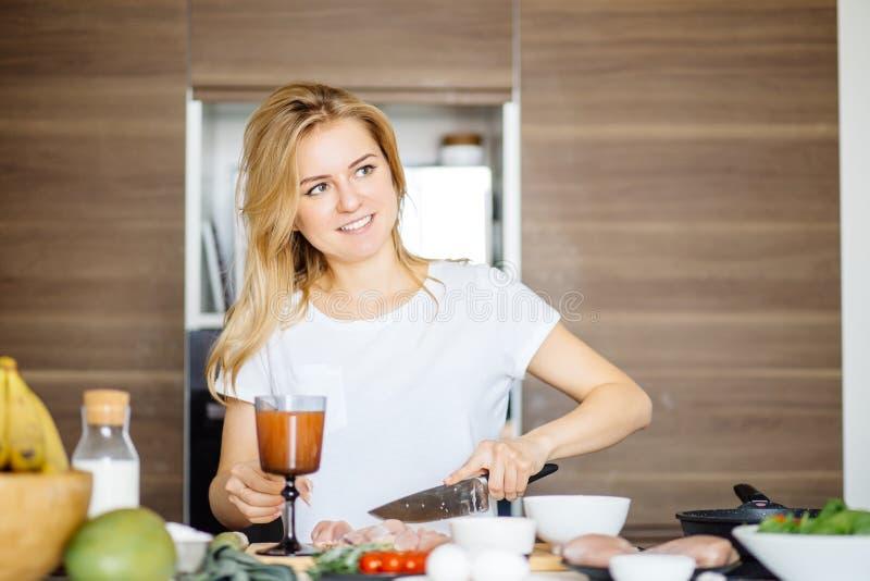 O corte da mulher chiken a carne em uma mesa de cozinha com uma faca grande do cozinheiro chefe imagens de stock royalty free