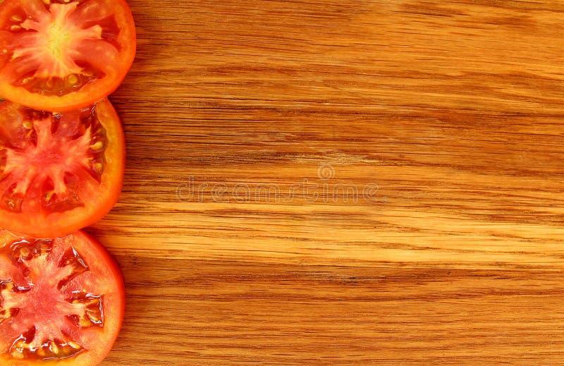 O corte dos tomates em partes encontra-se na borda de uma placa de corte imagens de stock