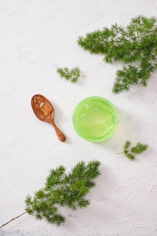 O cosmético desnata com as folhas no fundo de madeira branco da tabela fotos de stock