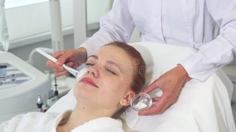 O Cosmetologist aplica o creme na cara do ` s do cliente imagem de stock