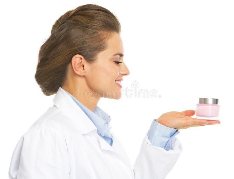 O cosmetologist de sorriso medica a mulher que apresenta a garrafa da nata imagem de stock