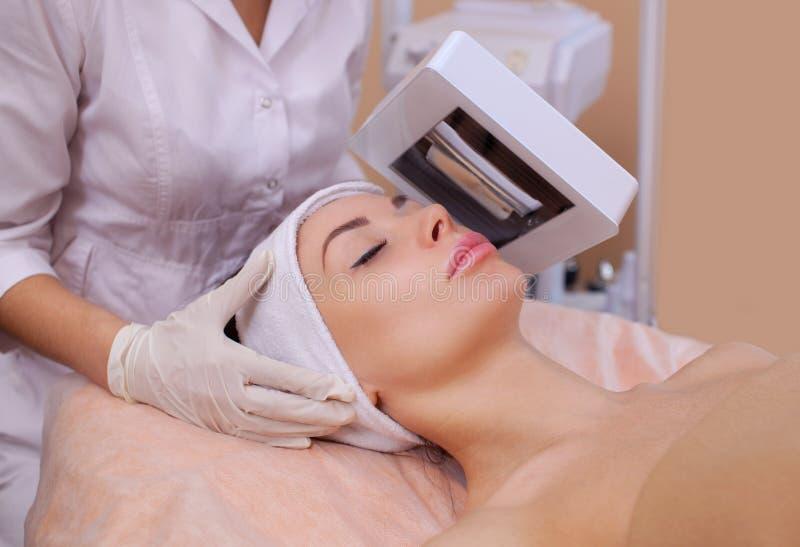 O Cosmetologist diagnostica com doença de pele de madeira da lâmpada do ` s, e igualmente revela áreas inflamadas na cara imagens de stock royalty free
