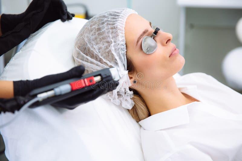 O cosmetologist do close-up faz um tratamento à cara da jovem mulher, procedimentos do laser do epilation da remoção do cabelo em imagens de stock