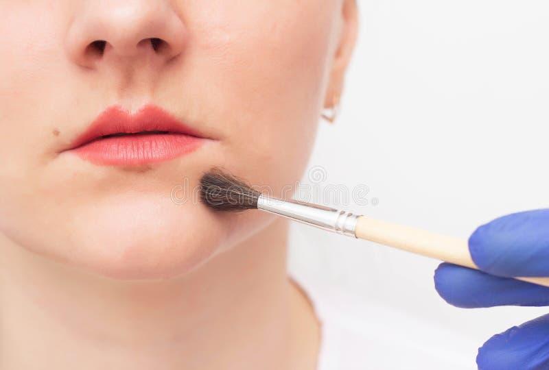 O cosmetologist do doutor conduz a casca química para que uma menina aumente os bordos, tatuagem imagens de stock royalty free