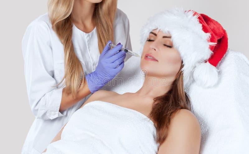 O cosmetologist do doutor faz a injeção na pele da cara e nos bordos de um bonito, jovem mulher no chapéu de Santa Claus foto de stock