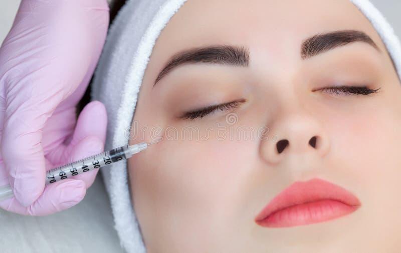 O cosmetologist do doutor faz o procedimento Botulinum da injeção da toxina para apertar e alisar enrugamentos na pele da cara imagens de stock