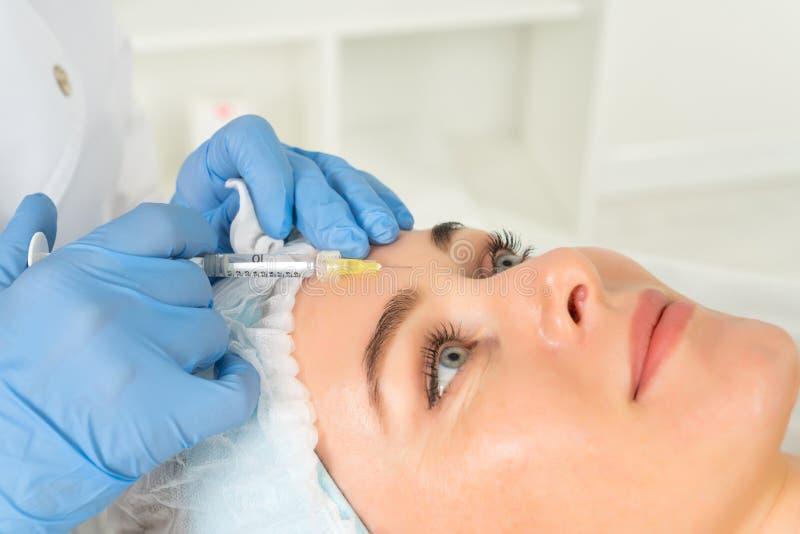 O cosmetologist do doutor faz o procedimento facial rejuvenescendo das injeções para apertar e alisar enrugamentos na pele da car fotos de stock royalty free