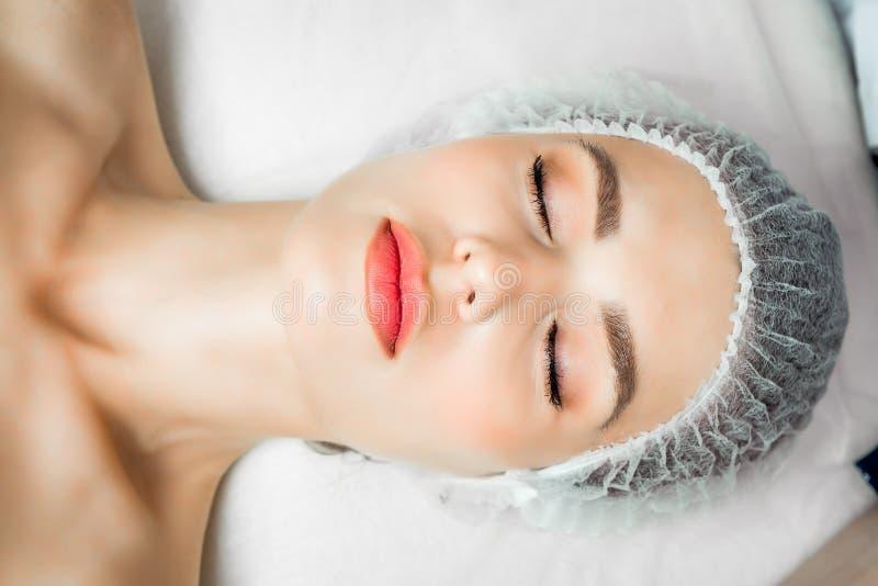 O cosmetologist do doutor faz o procedimento facial rejuvenescendo das injeções para apertar e alisar enrugamentos no foto de stock royalty free