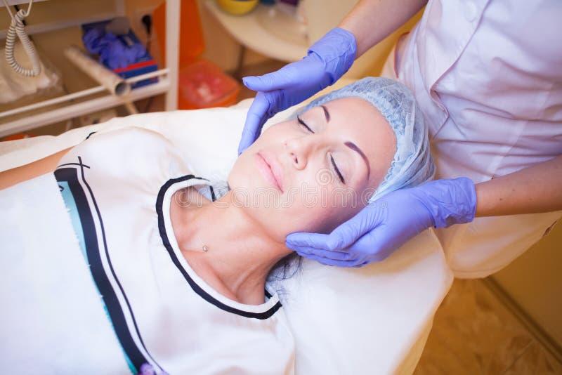 O cosmetologist do doutor faz uma massagem de cara da mulher fotografia de stock