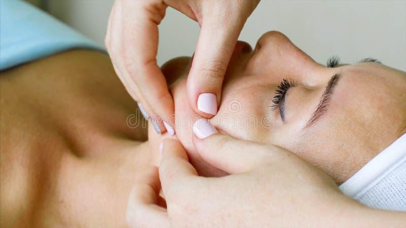 O cosmetologist do terapeuta da massagem faz a massagem facial para a mulher na clínica da beleza foto de stock