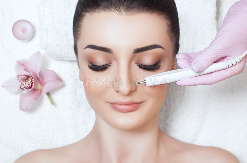 O cosmetologist faz ao instrumento um procedimento da terapia de um bonito, jovem mulher de Microcurrent em um salão de beleza fotografia de stock