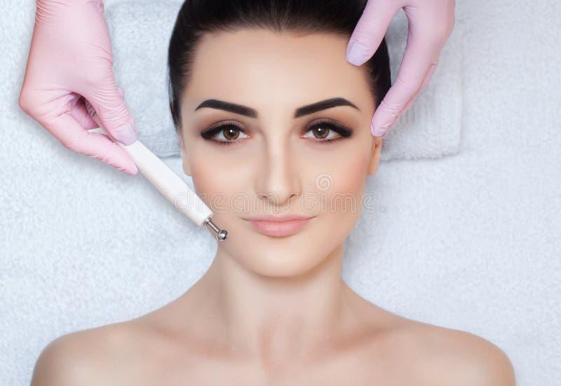 O cosmetologist faz ao instrumento um procedimento da terapia de um bonito, jovem mulher de Microcurrent em um salão de beleza foto de stock