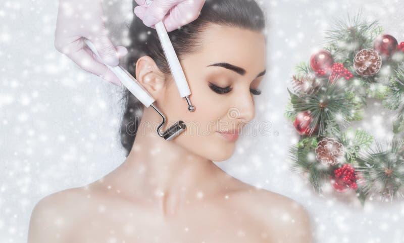 O cosmetologist faz o procedimento da terapia de Microcurrent de uma mulher bonita em um salão de beleza fotos de stock