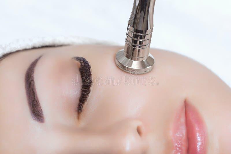 O cosmetologist faz o procedimento Microdermabrasion da pele facial de um bonito, jovem mulher fotografia de stock