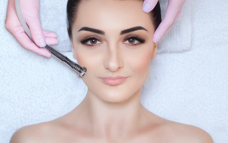 O cosmetologist faz o procedimento Microdermabrasion da pele facial de um bonito, jovem mulher em um salão de beleza imagem de stock