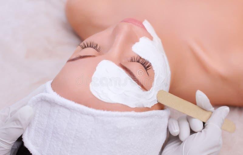 O cosmetologist para o procedimento de limpar e de hidratar a pele, aplicando uma máscara com a vara à cara imagens de stock royalty free