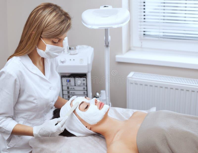 O cosmetologist para o procedimento de limpar e de hidratar a pele, aplicando uma máscara com a vara à cara de um woma novo foto de stock royalty free
