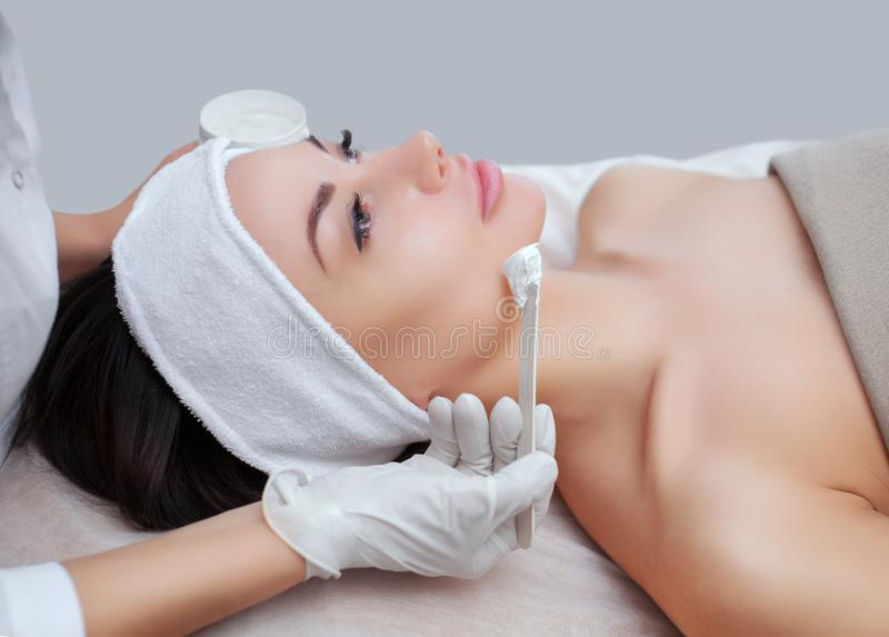 O cosmetologist para o procedimento de limpar e de hidratar a pele, aplicando uma máscara com a vara à cara de um woma novo fotografia de stock
