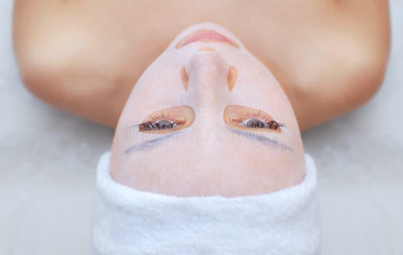 O cosmetologist para o procedimento de limpar e de hidratar a pele, aplicando uma máscara da folha à cara de uma jovem mulher no  fotos de stock