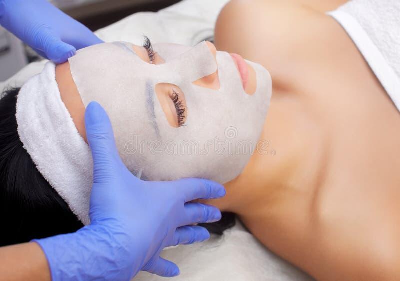 O cosmetologist para o procedimento de limpar e de hidratar a pele, aplicando uma máscara da folha à cara de uma jovem mulher no  imagens de stock royalty free