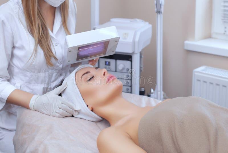 O cosmetologist usa a lâmpada de madeira para diagnóstico detalhado da condição de pele fotos de stock royalty free