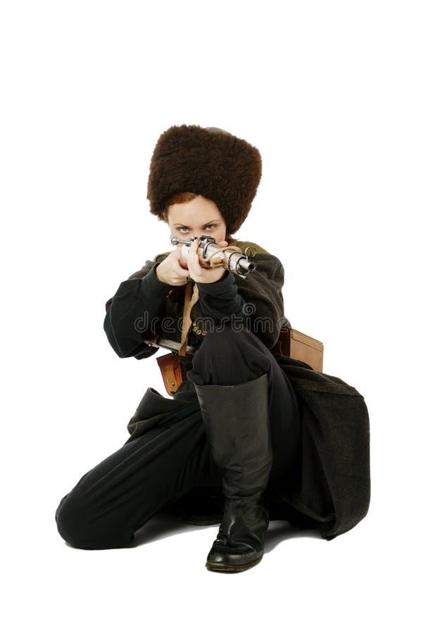 O Cossack aponta um rifle na posição squatting. fotografia de stock