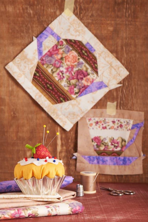 O coxim do pino como um queque com blocos da morango e dos retalhos do copo e do bule com um teste padrão das flores fotos de stock royalty free