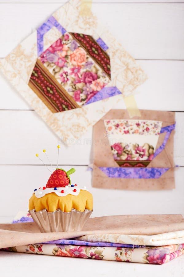 O coxim do pino como um queque com blocos da morango e dos retalhos do copo e do bule com um teste padrão das flores imagem de stock