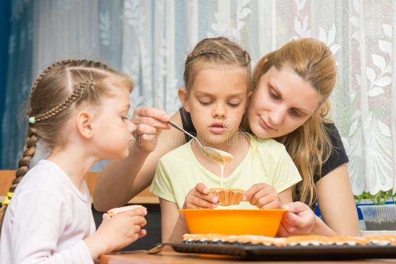 O cozimento da mãe e das duas crianças derrama a massa nos moldes que preparam queques para a Páscoa imagem de stock