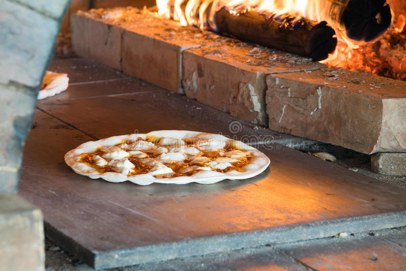 O cozimento fino da pizza da crosta na madeira ateou fogo ao forno fotografia de stock