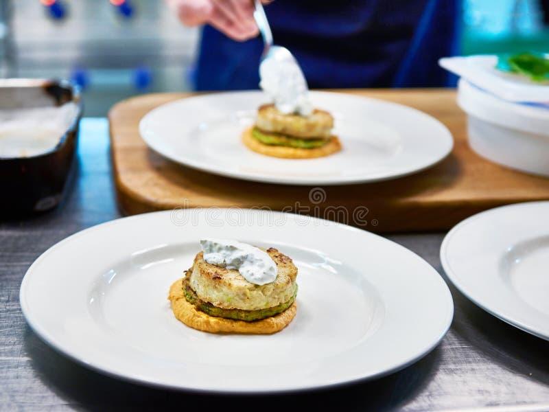 O cozinheiro é prato servido com a costoleta dos peixes no restaurante foto de stock