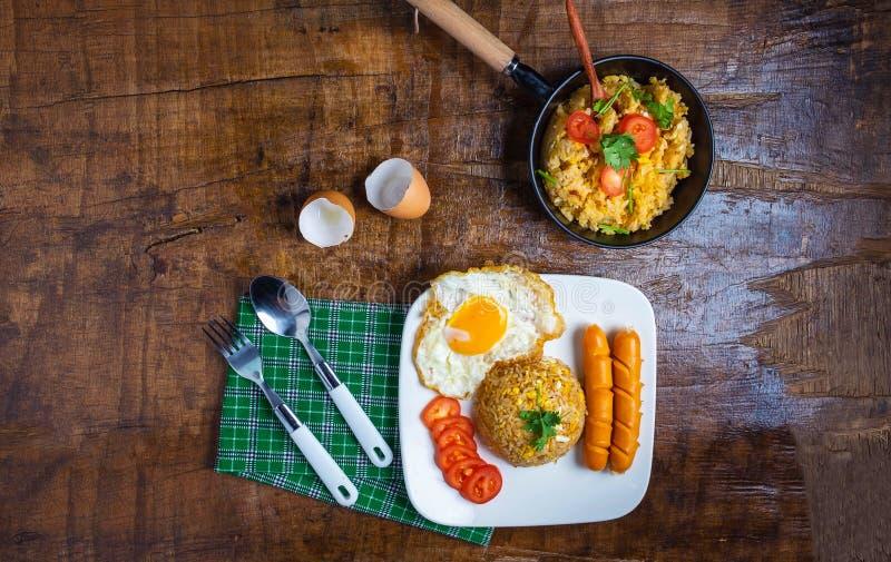 O cozinheiro American fritou o arroz em uma bandeja, servida com ovos fritos e salsichas fotografia de stock royalty free