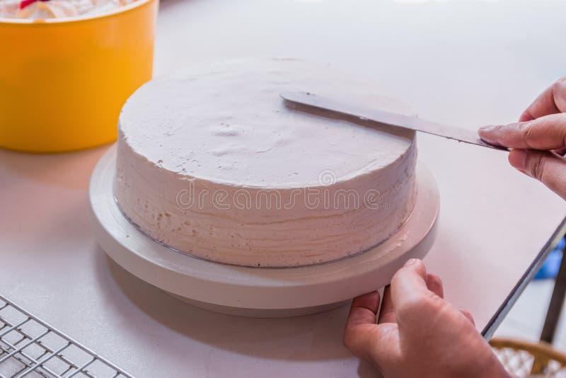 O cozinheiro chefe é bolo do crepe, o cozinheiro chefe está fazendo um chantiliy antes de cortar em uma parte imagem de stock
