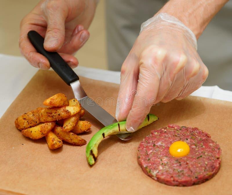 O cozinheiro chefe é servir tartare com batatas fritas e abacate foto de stock