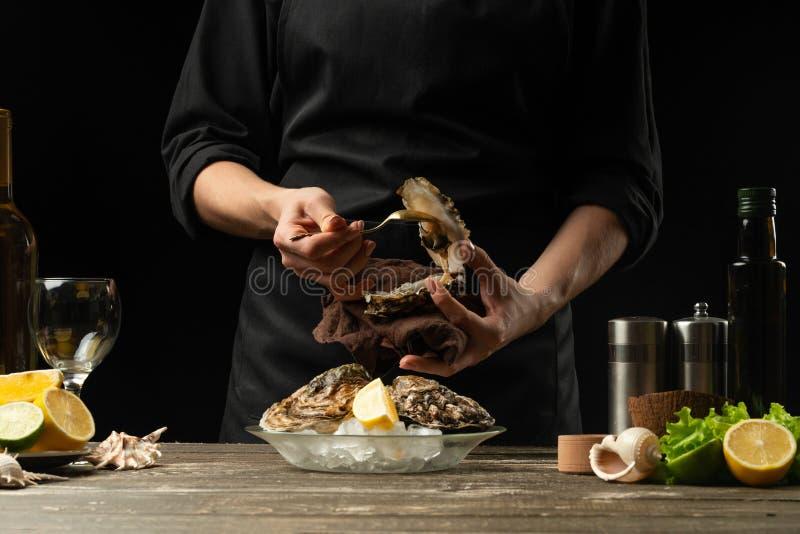 O cozinheiro chefe abre e limpa a ostra crua contra um fundo do vinho branco, da alface, dos limões e dos cais foto de stock