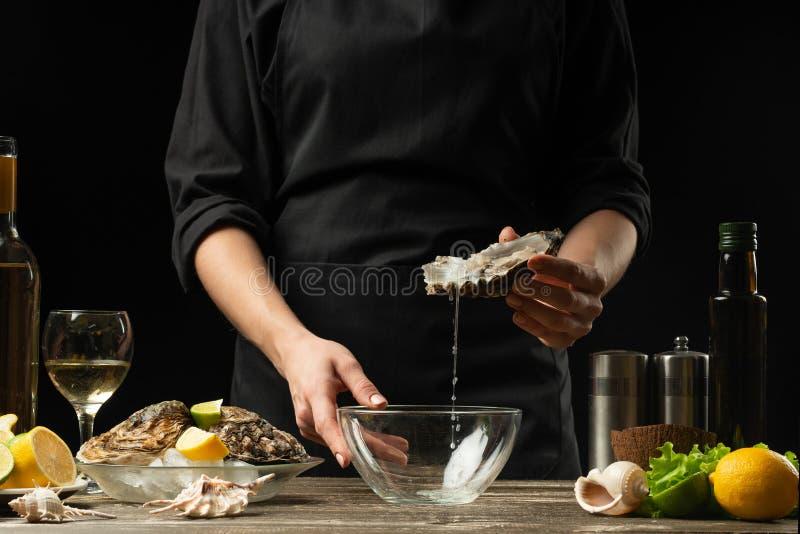 O cozinheiro chefe abre e limpa a ostra crua contra um fundo do vinho branco, da alface, dos limões e dos cais imagens de stock