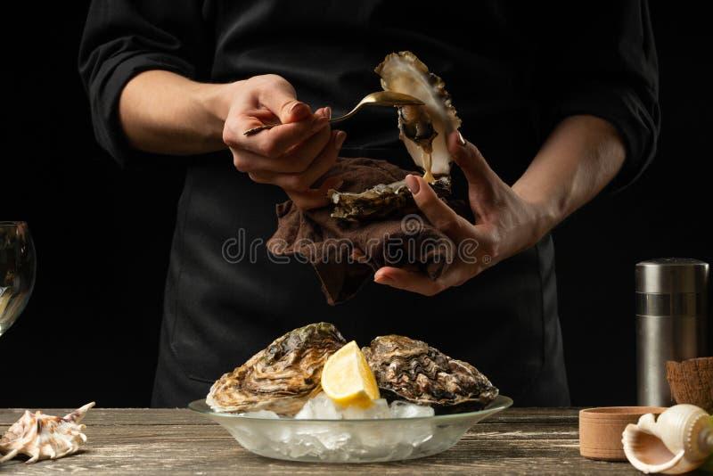 O cozinheiro chefe abre e limpa a ostra crua contra um fundo do vinho branco, da alface, dos limões e dos cais imagem de stock royalty free
