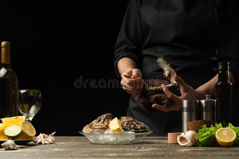 O cozinheiro chefe abre e limpa a ostra crua na perspectiva do vinho branco, da alface, dos limões e dos cais Com espaço para foto de stock