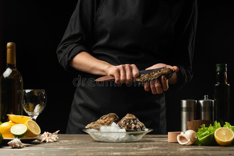 O cozinheiro chefe abre a faca e limpa a ostra crua, no fundo do vinho branco, da alface, dos limões e dos cais foto de stock