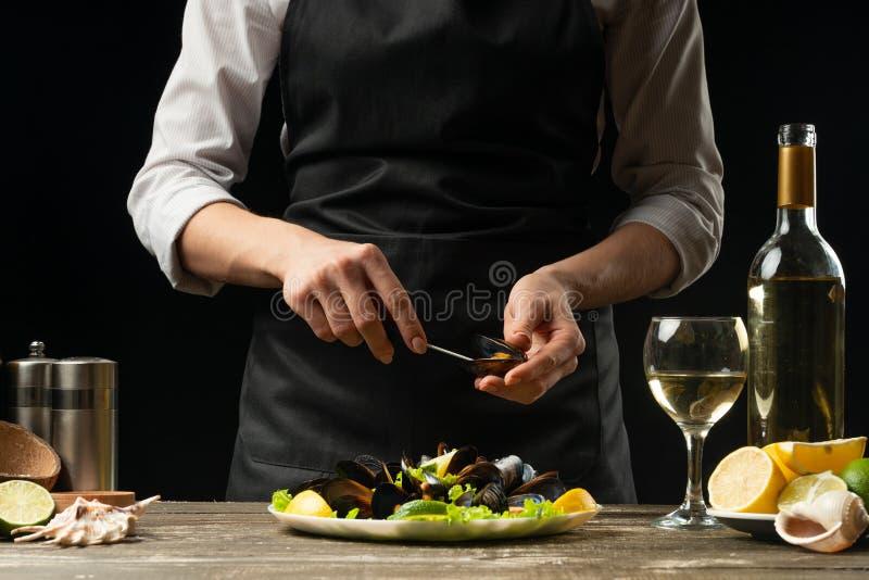 O cozinheiro chefe abre uma faca com mexilhões com uma salada com vinho branco, em um fundo escuro, no conceito do restaurante, n fotos de stock royalty free