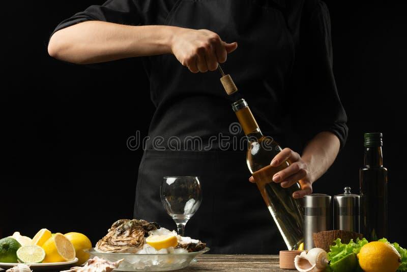 O cozinheiro chefe abre o vinho seco italiano com as ostras com limão, em um fundo escuro fotografia de stock royalty free